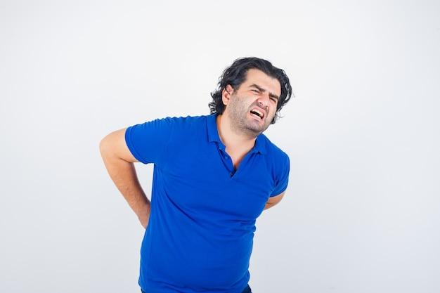 青いtシャツの腰痛に苦しんでいる成熟した男性と倦怠感。正面図。
