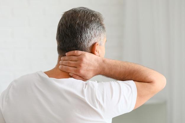 Зрелый мужчина страдает от боли в шее дома