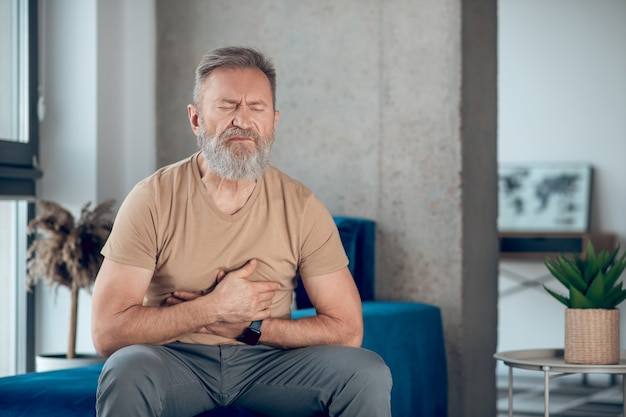 A mature man suffering from a stomach ache