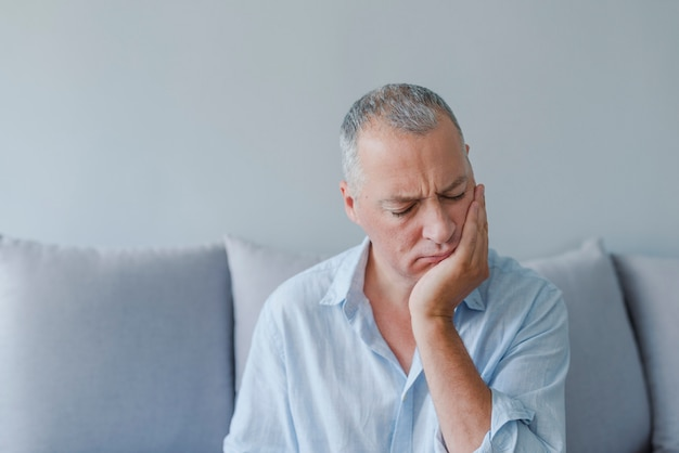 Mature man suffering from tooth pain, caries