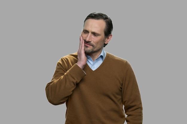 歯痛に苦しんでいる成熟した男。灰色の背景に強い歯痛を持つ男の肖像画。耐え難い歯の痛み。