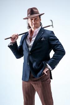 L'uomo maturo in un vestito e un cappello che tiene il bastone.