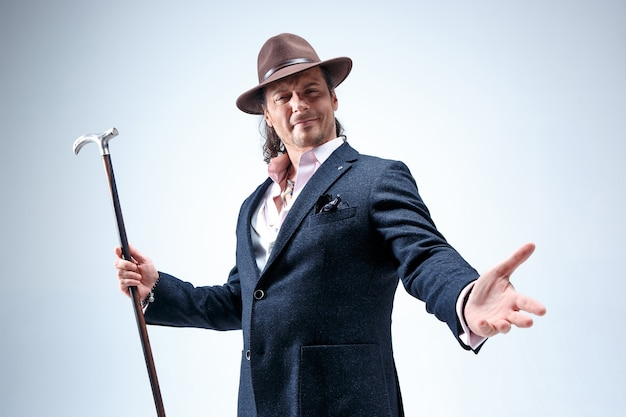 The mature man in a suit and hat holding cane.