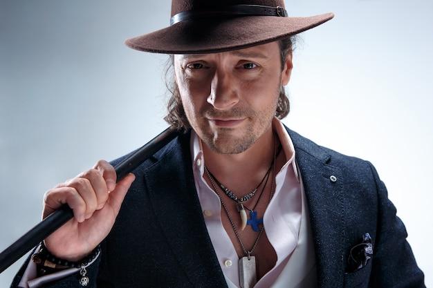 L'uomo maturo in giacca e cappello con canna.