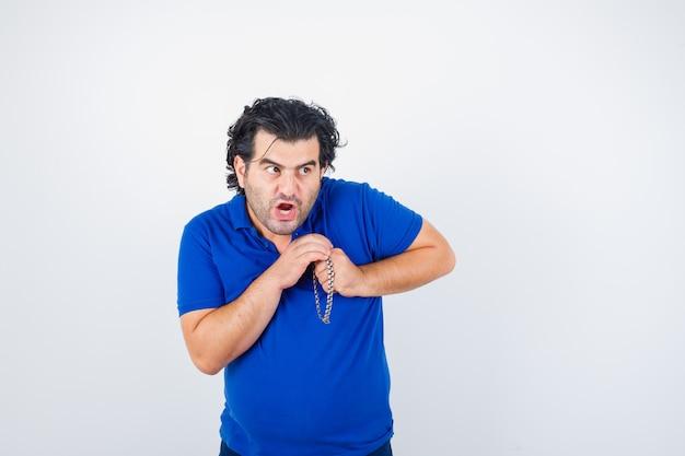 Uomo maturo in t-shirt che guarda lontano tenendo le mani vicino al petto e guardando spaventato, vista frontale.