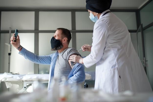 예방 접종, 코로나바이러스 및 예방 접종 개념을 받을 때 셀카를 찍는 성숙한 남자.
