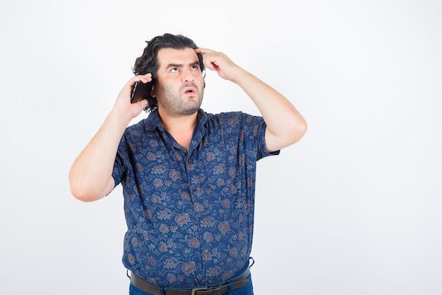 Зрелый человек разговаривает по мобильному телефону в рубашке и смотрит задумчиво, вид спереди.