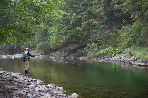 Mature man throwing fishing rod into mountain river. professional fisherman in special outfit standing outdoors and fishing.