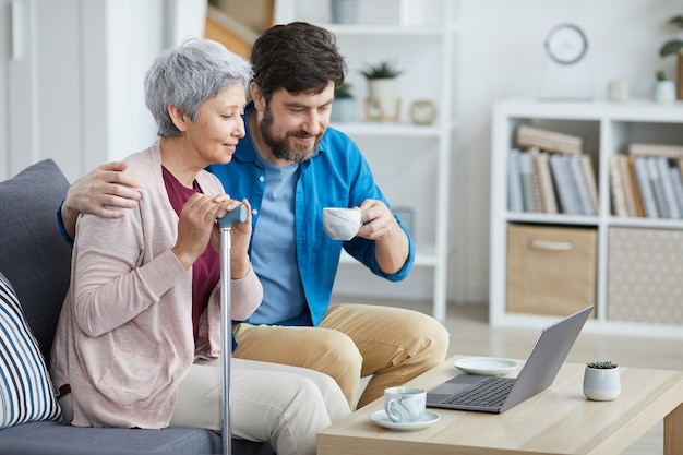 Mature man together with senior woman sitting on sofa watching movie online on laptop and drinking tea in the room at home