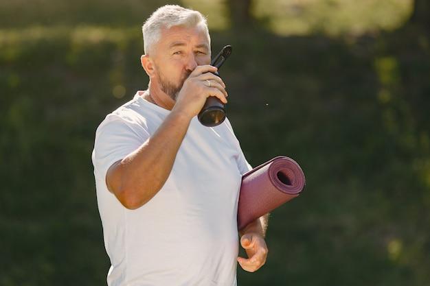 中年の男性が夏の公園でトレーニングします。マットと立っているシニア。スポーツ服の老人。