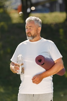 Mature man training in a summer park. senior standing with a mat. old man in a sports clothes.