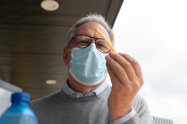 마스크를 쓰고 프렌치 프라이를 먹으려는 성숙한 남자