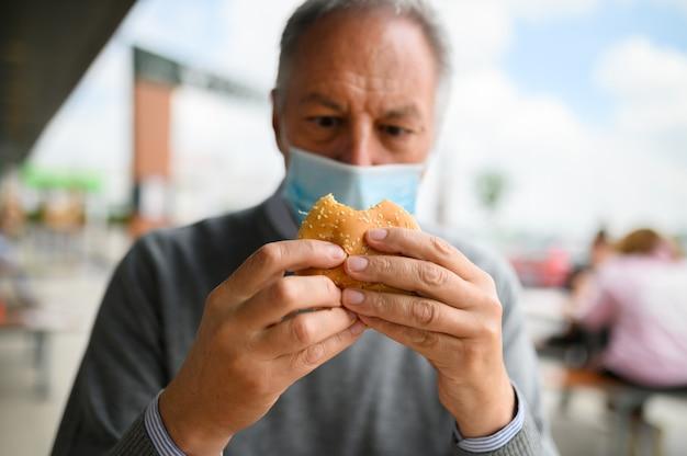 마스크를 쓰고 햄버거를 먹으려 고 노력하는 성숙한 남자