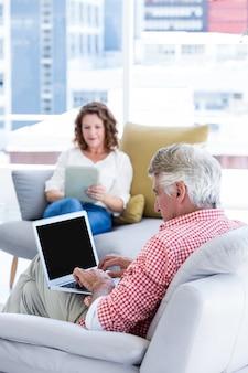 Зрелый человек, набрав на ноутбуке, сидя у женщины