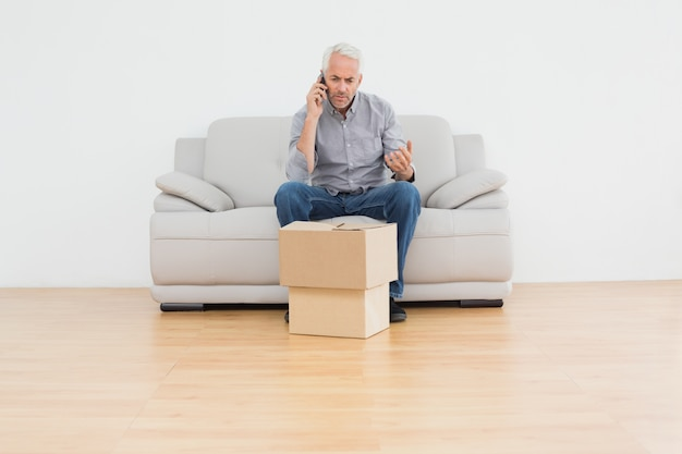 Mature man using cellpone on sofa with boxes in a house