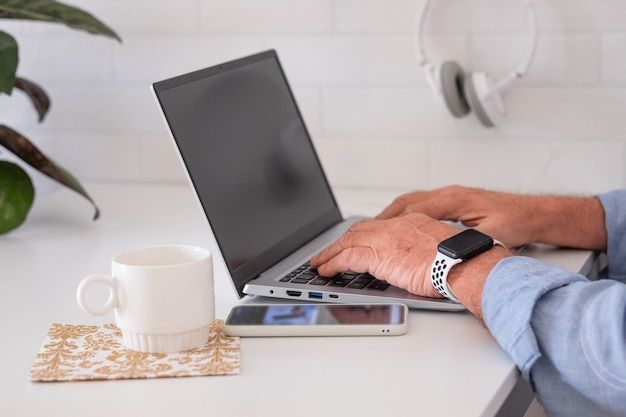 Mature man using laptop computer at home business man working in office freelance technology