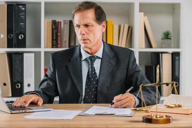 Mature man using laptop while checking the document paper in the courtroom