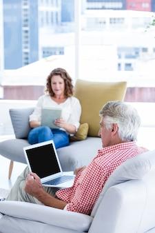 Зрелый человек, используя ноутбук, сидя у женщины