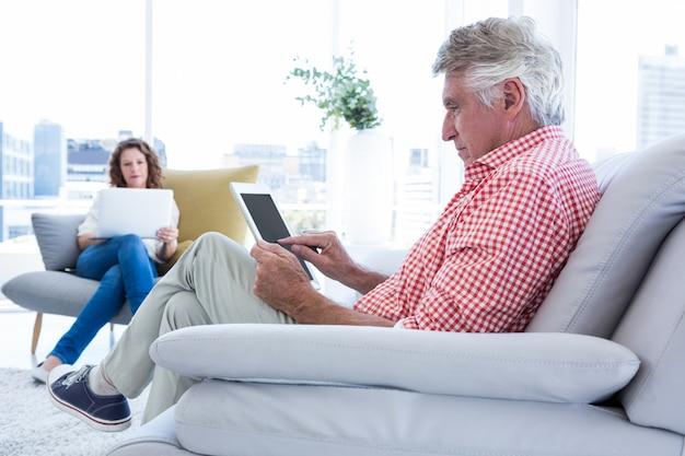 Зрелый человек с помощью планшетного компьютера сидя
