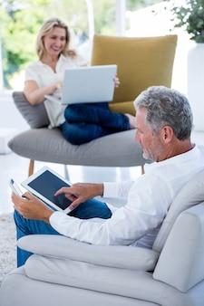 Зрелый человек используя таблетку пока женщина держа компьтер-книжку