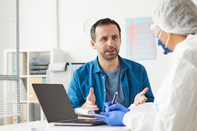 成熟した男性が彼の医者を訪問し、彼は座ってオフィスで彼の苦情について話します