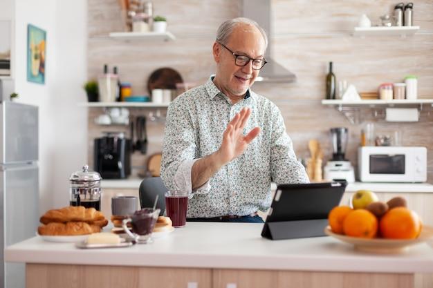 朝食を楽しんでいるキッチンでビデオ通話中に会話しながら手を振る成熟した男。インターネットオンラインチャット技術、仮想電話会議用のタブレットウェブカメラを使用している高齢者