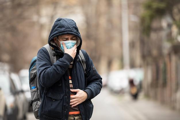 성숙한 남자는 마을에 서있는 동안 얼굴 마스크를 쓰고 기침을합니다.