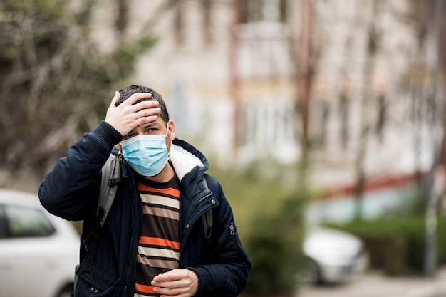 Mature man wear face mask and coughing while standing in the town.