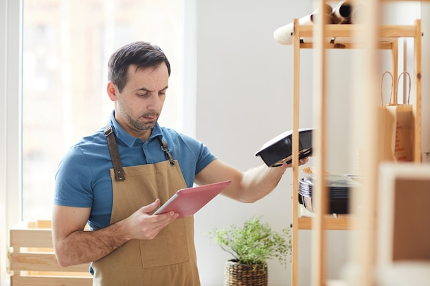 Mature man wearing apron using digital table while doing inventory in food delivery service