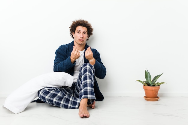 Mature man wearing pajama sitting on house floor showing that she has no money.