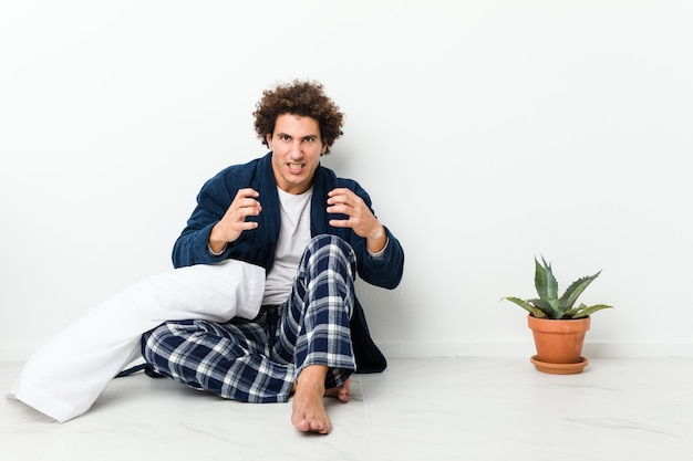 Mature man wearing pajama sitting on house floor upset screaming with tense hands.