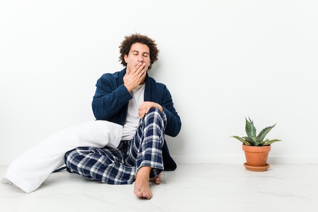 Mature man wearing pajama sitting on house floor yawning showing a tired gesture covering mouth with hand.