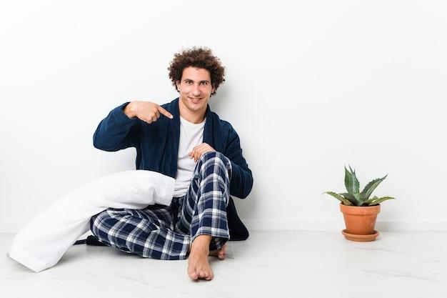 シャツのコピースペースを手で指している家の床の人に座ってパジャマを着て、誇りと自信を持って成熟した男
