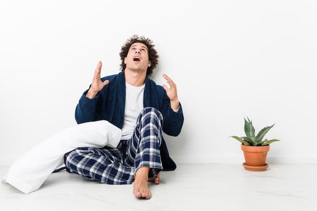Зрелые мужчины носить пижаму, сидя на полу дома кричать в небо, глядя вверх, разочарованы.