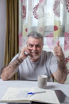 Зрелый человек с бородой работает на дому