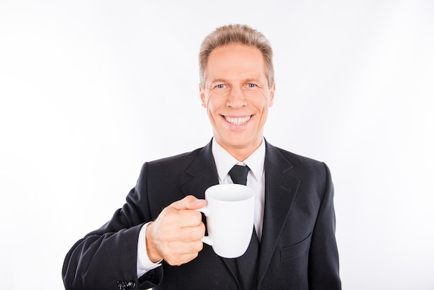 手にカップを持つ成熟した男