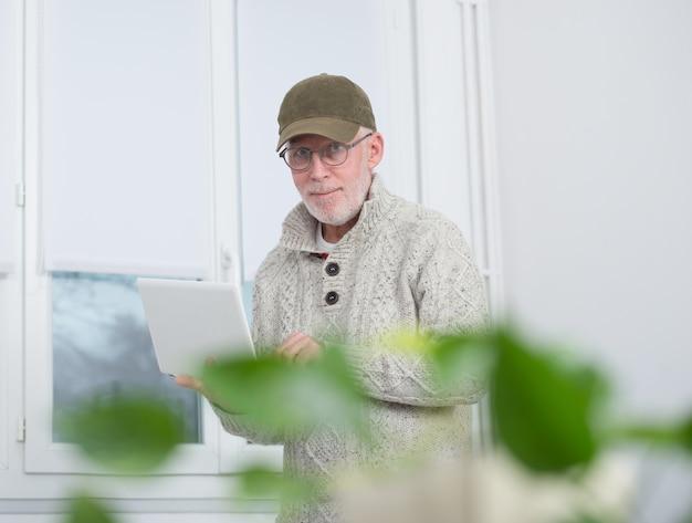 Mature man with  baseball cap using a laptop