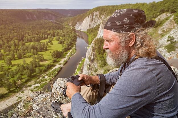 ひげとバンダナを身に着け、頭に縛られた成熟した男は、カメラを手に崖の上に休んでいます。その下には静かな川のある樹木が茂った風景があります。