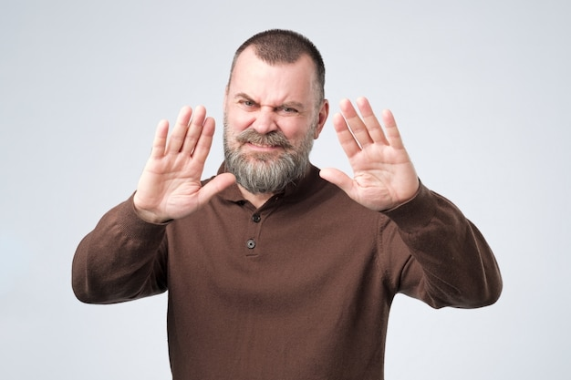 Зрелый мужчина с бородой показывает жест отказа, не хочет с вами разговаривать