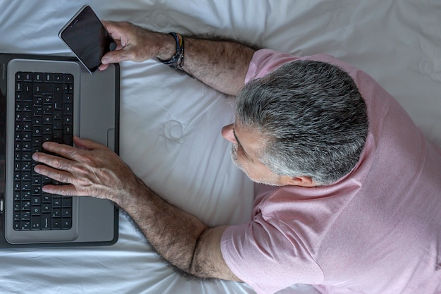 Mature man with beard working in the bed