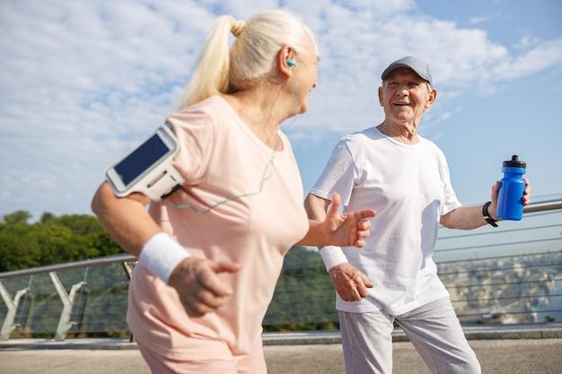 Зрелый мужчина с бутылкой воды и жена вместе бегут по мосту