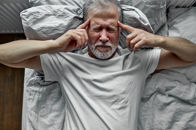 Mature man with closed eyes lying in bed, touching temples close up, tired older male suffering from headache or migraine, feeling unwell, suffering from insomnia, lack of sleep