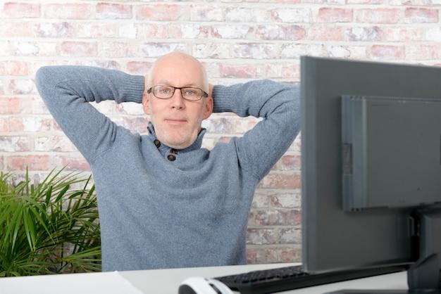 コンピューターを持つ成熟した男は彼のオフィスでリラックスしています