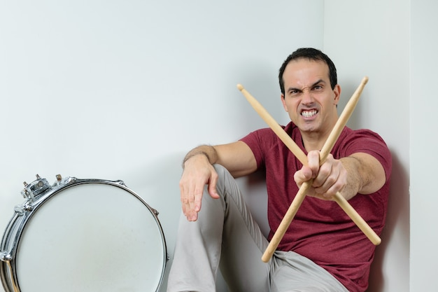 Mature man with a drum and sticks