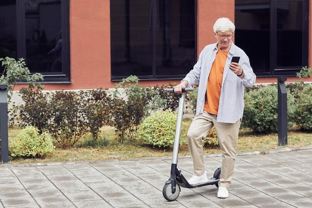 Зрелый мужчина с электросамокатом в городе