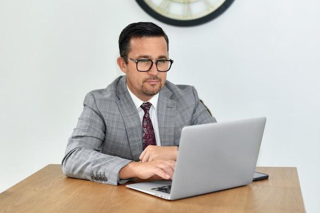 眼鏡をかけた成熟した男はコンピューターで働く