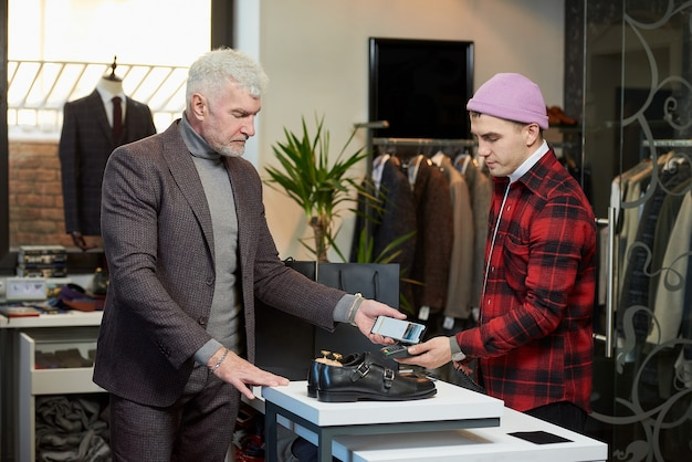 A mature man with gray hair and a sporty physique is applying a cellphone to a point of sale terminal in a clothing store. a male customer with a beard is paying to a shop assistant in a boutique.