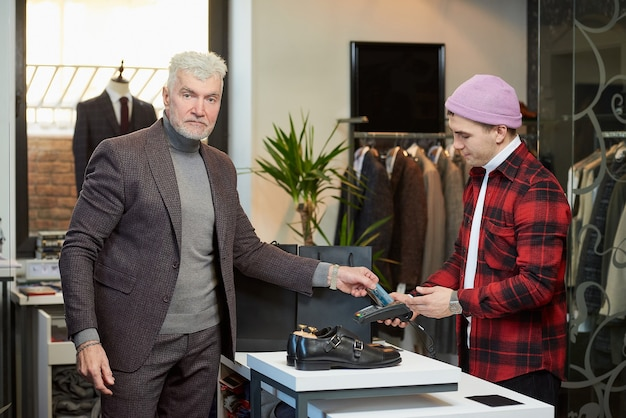 A mature man with gray hair and a sporty physique is applying a credit card to a point of sale terminal in a clothing store. a male customer with a beard and a shop assistant in a boutique.