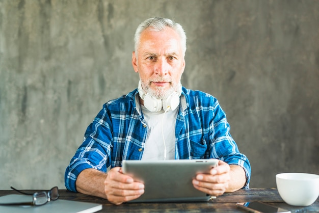 Mature man with headphone around his neck holding digital tablet