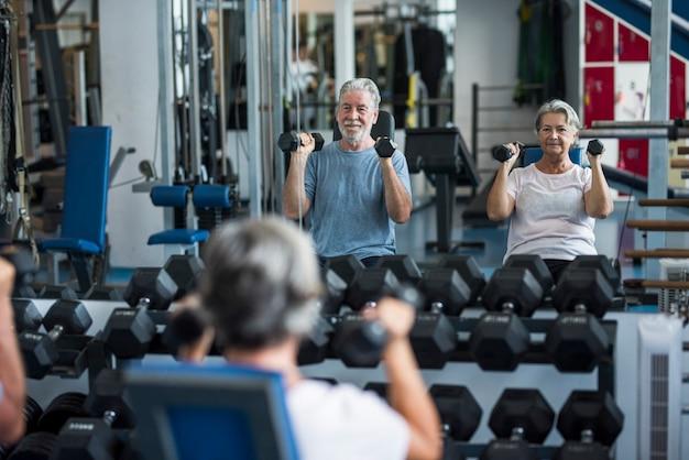 ジムで上腕二頭筋の運動をしている妻と一緒に成熟した男性-フィットネスと健康的なライフスタイルの概念-一緒に体を訓練する-2人の先輩のカップル